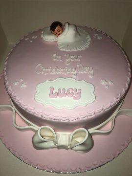Baby girl wrapped in blanket christening cake